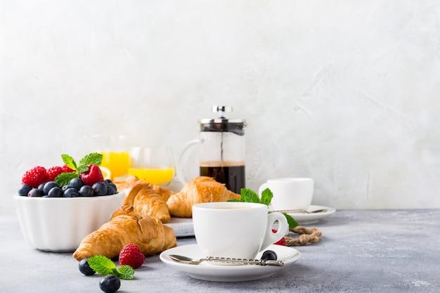Xícaras de café e croissants brancos Foto Premium