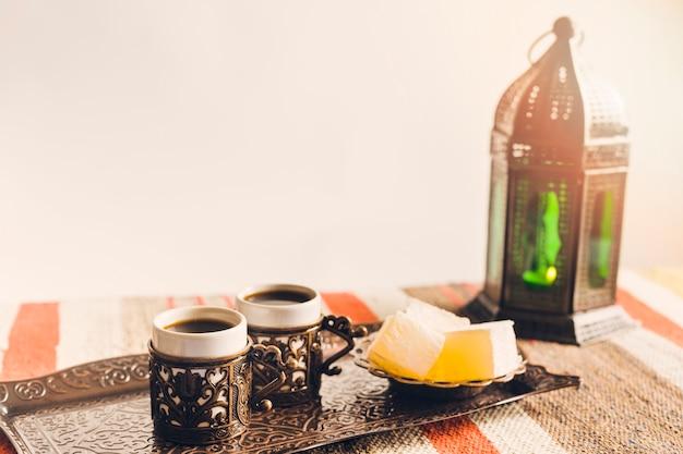 Xícaras de café perto de pires com doces delícias turcas na bandeja e lanterna Foto gratuita