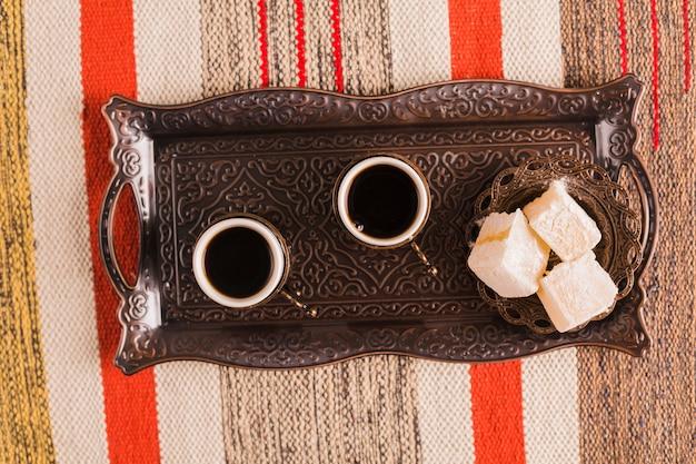 Xícaras de café perto de pires com doces delícias turcas na bandeja Foto gratuita