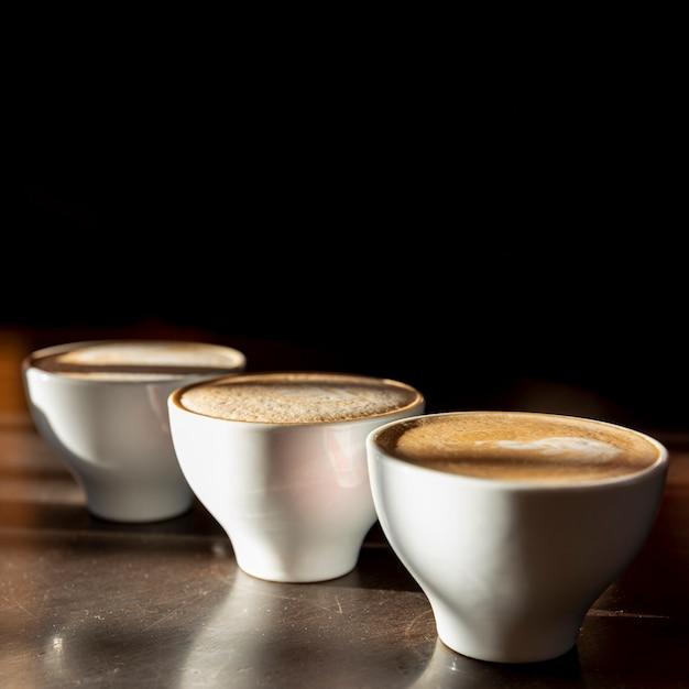 Xícaras de café saboroso close-up com leite Foto gratuita