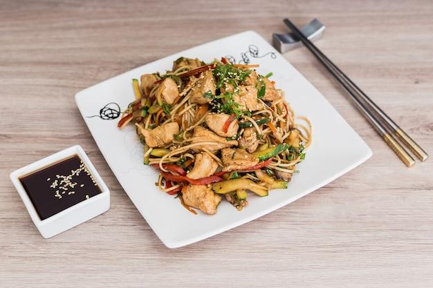 Yakisoba com molho de soja em uma mesa de madeira Foto Premium