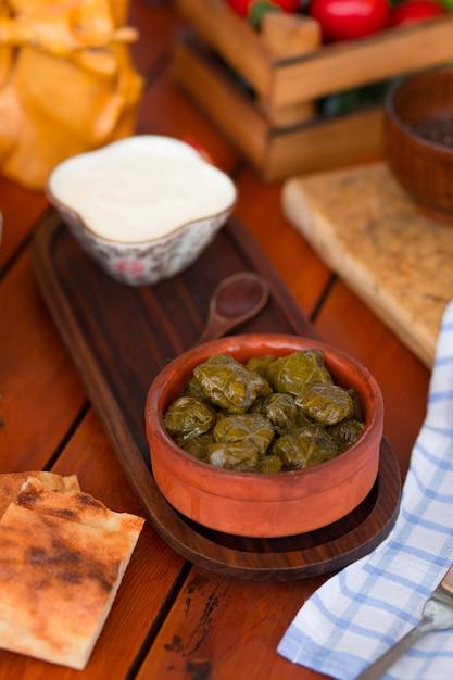 Yarpag dolmasi, yaprak sarmasi, folhas de uva verdes recheadas com arroz e carne na tigela de cerâmica com iogurte. Foto gratuita