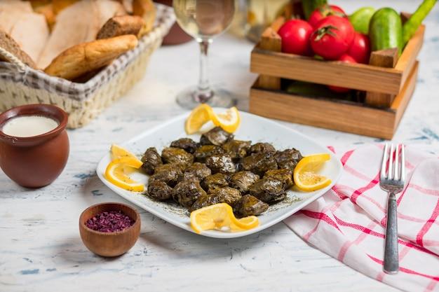 Yarpaq dolmasi, yaprak sarmasi, folhas verdes de uva cheias, recheadas com carne e arroz, servidas com limão Foto gratuita