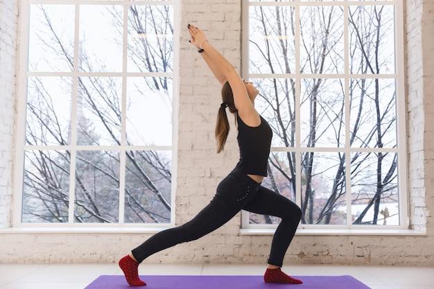 Yoga mulher fazendo virabhadrasana Foto Premium