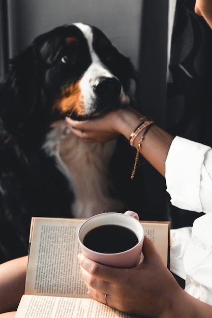 Yoman sentada na sala de estar com seu lindo cachorro bernese mountain dog, lendo e bebendo café. Foto Premium