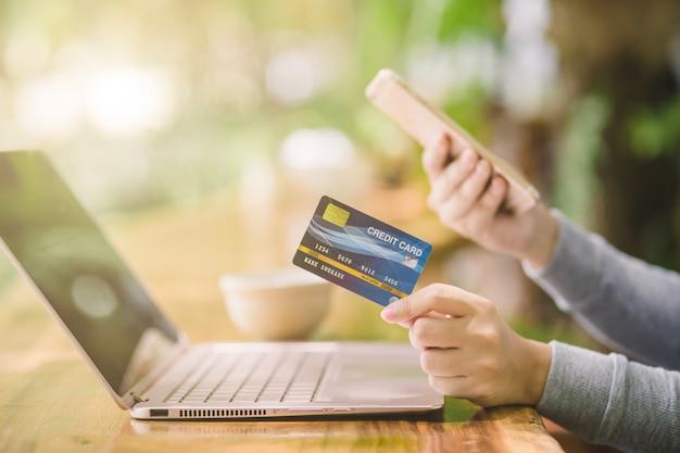 Yong feminino mão segurando o cartão de crédito de plástico e usando o laptop. compras on-line ou pagando conceito. Foto Premium
