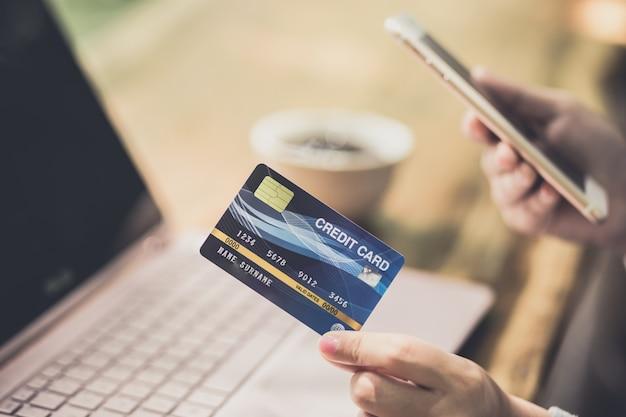 Yong mão feminina segurando o cartão de crédito plástico e usando o laptop. compras on-line ou conceito de pagamento. Foto Premium