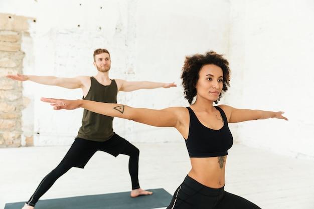 Youg homem africano e homem ruivo fazendo exercícios no ginásio Foto gratuita