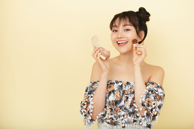 Younf atraente mulher aplicando blush nas bochechas de brincadeira Foto gratuita