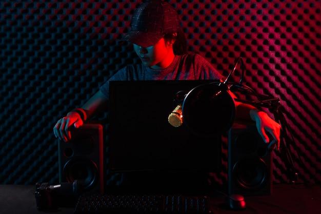 Young adult youtuber transmitido ao vivo no canal do youtube. mulher conectar mídia social com equipamentos profissionais, como teclado para jogos e-sport, mouse, monitor, alto-falante, câmera, estúdio, vermelho escuro Foto Premium