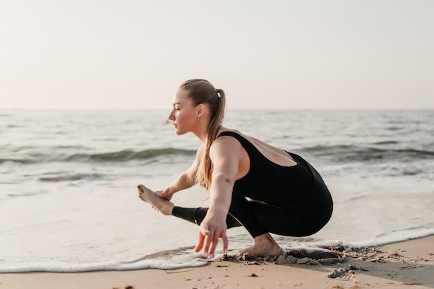 Young cabe mulher prática yoga asana na areia perto do oceano Foto Premium