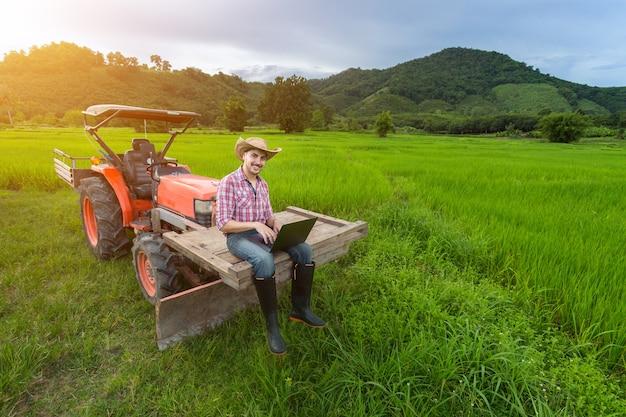Young farmer registrou crescimento de produtividade sentado em um trator. Foto Premium