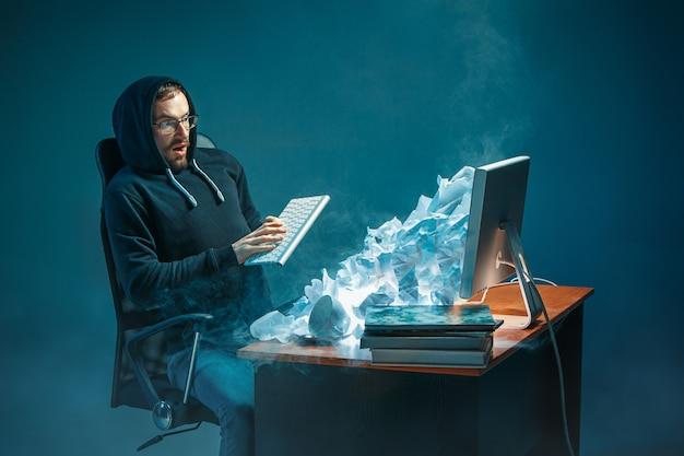 Young salientou o empresário bonito trabalhando na mesa no escritório moderno, gritando na tela do laptop e estar com raiva de spam Foto gratuita
