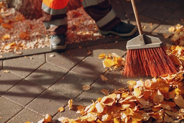Zelador de limpeza varrendo folhas de outono na rua | Foto Premium