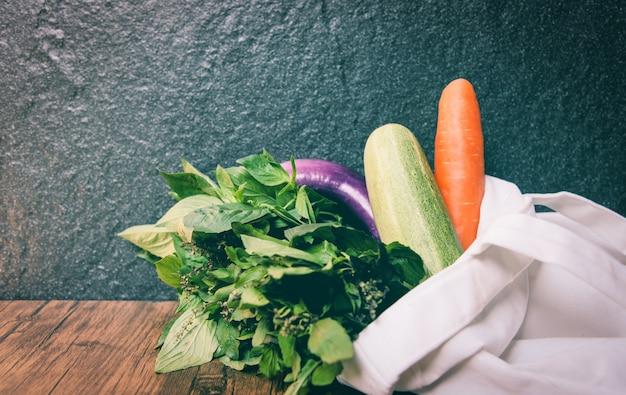 Zero desperdício usar menos conceito de plástico / legumes frescos orgânicos em sacos de tecido de algodão ecológico na mesa de madeira branco bolsa de lona saco de pano de mercado de compras de plástico livre Foto Premium