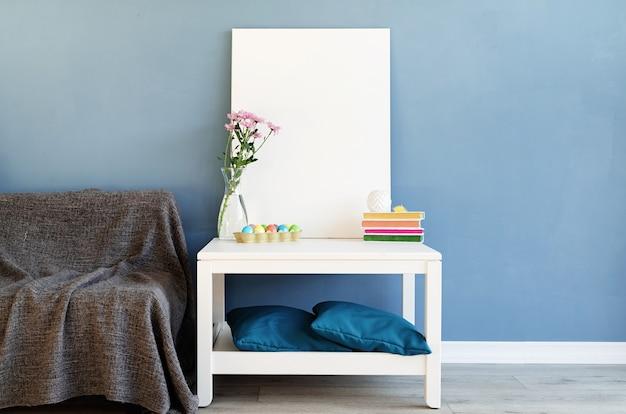 Zombe de moldura branca na mesa de centro na sala azul. tela em branco em branco no interior Foto Premium