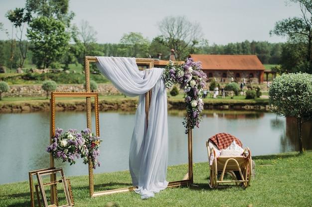 Zona de fotos em um casamento perto do lago com uma cadeira. decoração de casamento de verão para convidados. Foto Premium