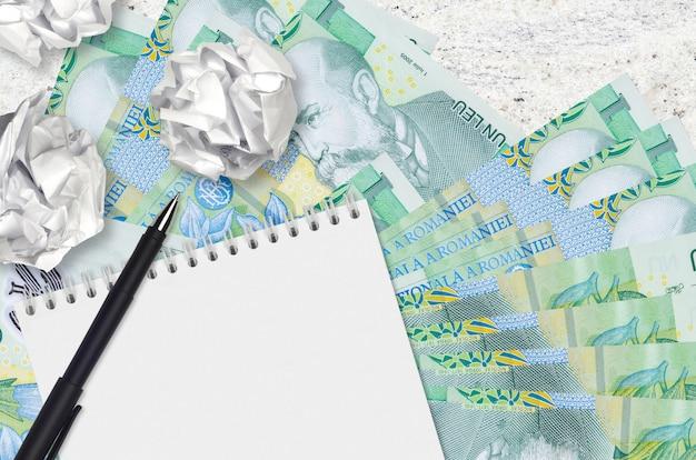 1 rumänische leu-scheine und zerknitterte papierkugeln mit leerem notizblock. schlechte ideen oder weniger inspirationskonzept. ideen für investitionen suchen Premium Fotos