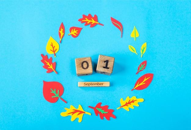1. september auf einem hölzernen kalender auf einem blauen hintergrund unter dem papierherbstlaub Premium Fotos