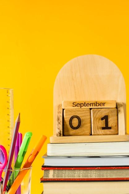 1. september auf einem hölzernen kalender unter lehrbüchern und stiften, um auf einem gelben hintergrund zu studieren Premium Fotos