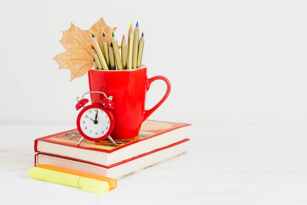 1. september konzept. roter wecker, tasse, farbstifte, bücher und ahornblatt. zurück zum schulkonzept Premium Fotos