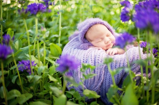 17 tagesaltes lächelndes neugeborenes baby schläft auf seinem magen im korb auf natur im garten im freien. Premium Fotos