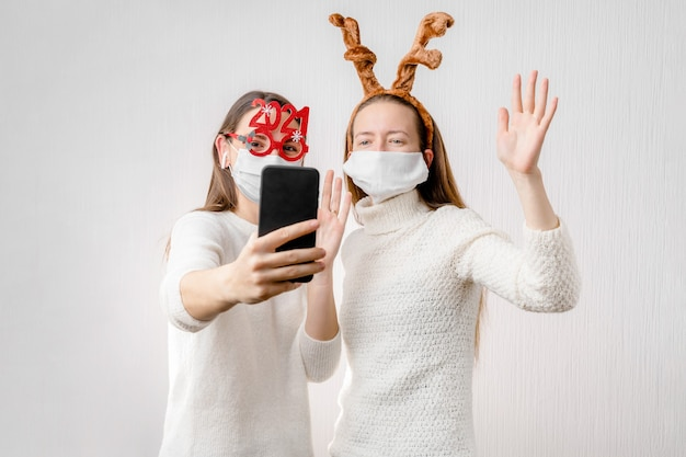 2 junge mädchen oder junge frau mit weihnachtsmütze und gesichtsmaske machen online-videoanruf. quarantäne Premium Fotos