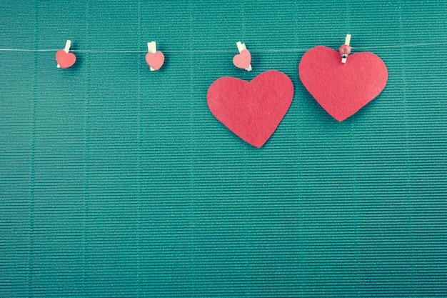 2 rote herzen und hangline mit grünem hintergrund, valentinsgrußkonzept Premium Fotos