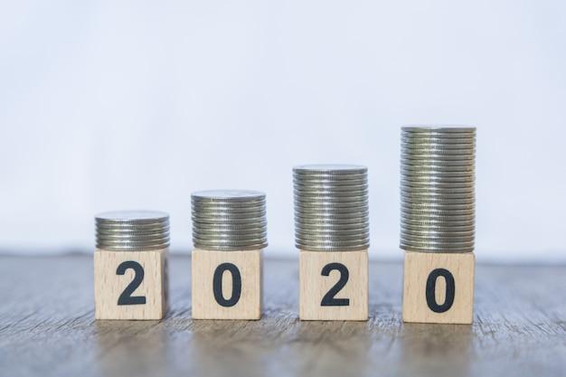 2010 neujahr, geld und wirtschaft. schließen sie oben vom stapel münzen auf zahlholzklotzspielzeug auf hölzerner tabelle und weiß. Premium Fotos
