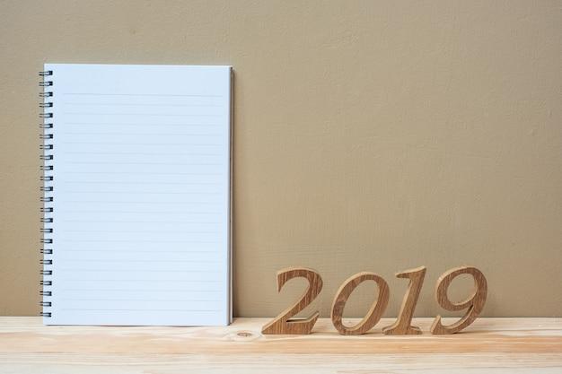 2019 glückliche neue jahre mit notizbuch und hölzerner zahl auf tabelle Premium Fotos