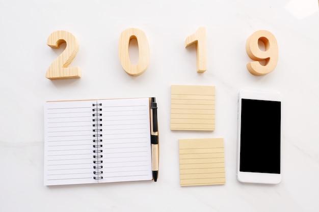 2019 hölzerne buchstaben, leeres briefpapier, intelligentes telefon auf weißem hintergrund Premium Fotos