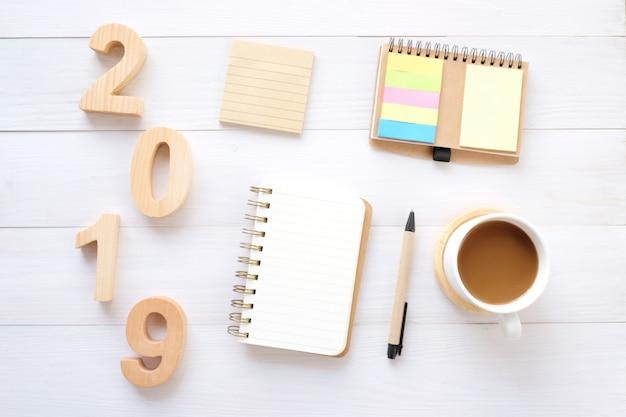 2019 hölzerne buchstaben, leeres notizpapier und kaffee auf weißem tabellenhintergrund Premium Fotos