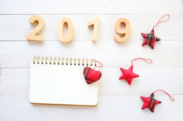 2019 holzbuchstaben, leeres notizbuchpapier und verzierung auf weißem hölzernem hintergrund Premium Fotos