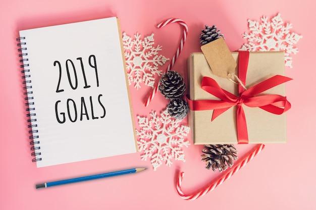 2019 ziele des neuen jahres, braune geschenkbox von oben, notizbuch und weihnachtsdekoration Premium Fotos