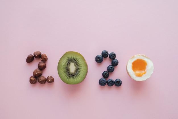 2020 gemacht von der gesunden nahrung auf rosafarbenem pastellhintergrund, healhty auflösungdiät des neuen jahres und lebensstil Premium Fotos
