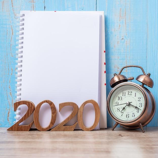2020 guten rutsch ins neue jahr mit leerem notizbuch, retro- wecker und hölzerner zahl. Premium Fotos