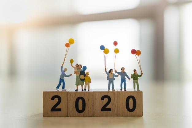 2020 neues jahr und familienkonzept. schließen sie oben von der gruppe kinder- und kinderminiaturzahlen mit ballon auf hölzernem zahlenblock. Premium Fotos