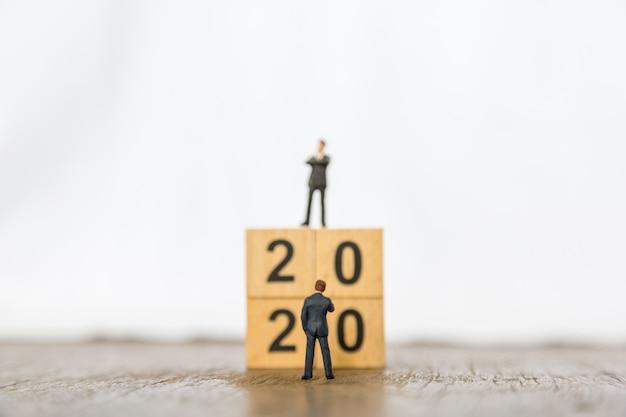 2020 neujahr und business planning. schließen sie oben von der miniaturzahl mit zwei geschäftsmännern, die vor stapel hölzernen zahlenblöcken steht Premium Fotos