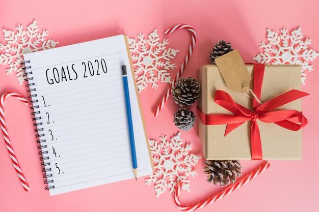 2020 neujahrskonzept. liste der ziele 2020 im notizblock, in der geschenkbox und in der weihnachtsdekoration auf rosa pastellfarbe mit kopienraum Premium Fotos
