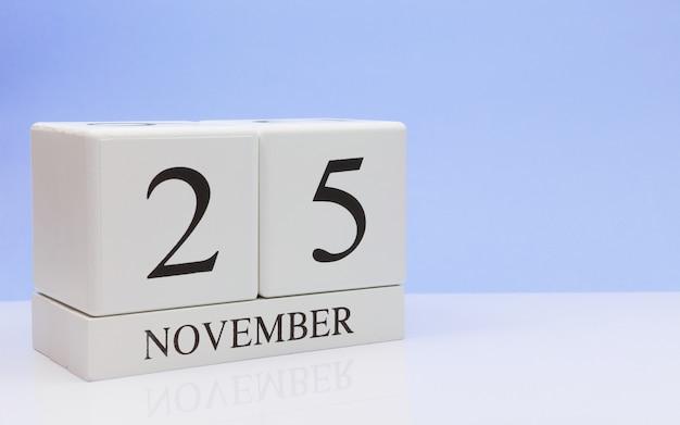 25. november tag 25 des monats, täglicher kalender auf weißer tabelle mit reflexion Premium Fotos
