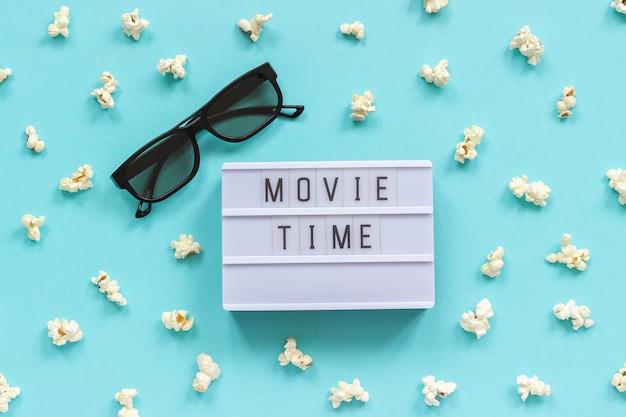 3d-brille, popcorn- und leuchtkasten-text filmzeit auf hintergrund des blauen papiers. Premium Fotos