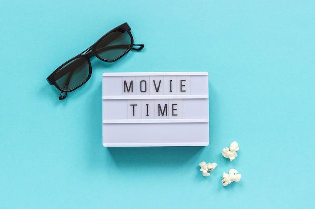 3d brille, popcorn und lightbox text filmzeit auf blauem papierhintergrund. Premium Fotos