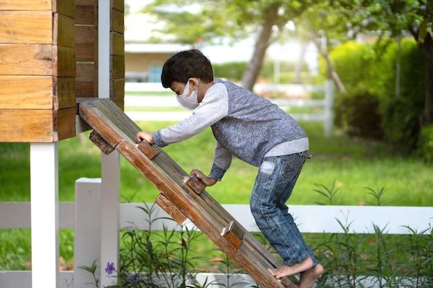 4-5 jahre alter asiatischer kleiner junge, der leiter auf spielplatz klettert. Premium Fotos