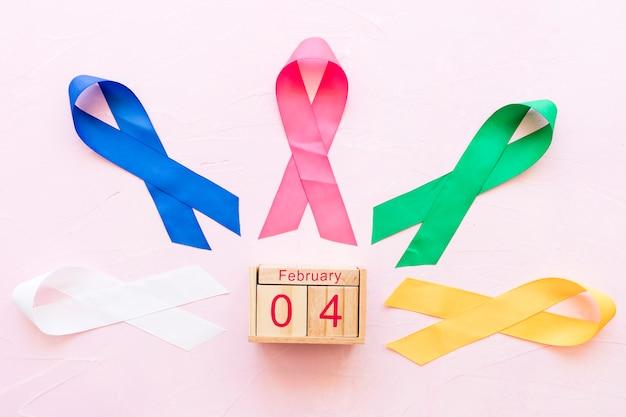 4. februar holzkiste um die bunten bänder auf rosa hintergrund Kostenlose Fotos