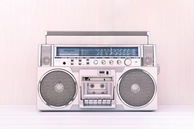 80er jahre retro-kassettenradio in silberner farbe auf hellem holzhintergrund. musikkonzept spielen. Premium Fotos