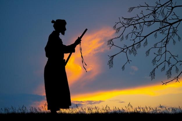 Abbildung des samurais mit katana am sonnenuntergang Premium Fotos
