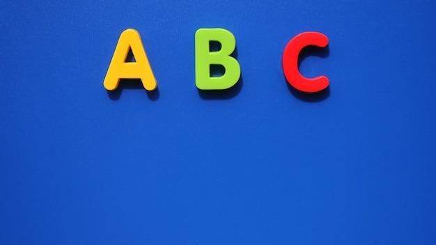 Abc-anfangsbuchstaben des englischen alphabets auf blauem hintergrund. englisch für anfänger. speicherplatz kopieren. Premium Fotos