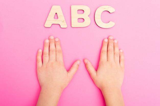 Abc-buchstaben in den kinderhänden auf rosa hintergrund Premium Fotos
