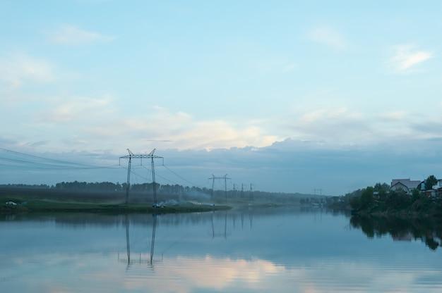 Abend neblige landschaft der landschaft. der fluss ist im nebel. drähte der elektrischen spannung. Premium Fotos