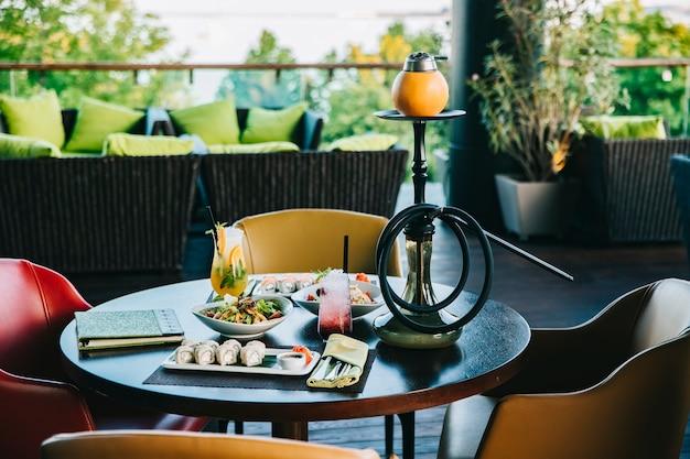 Abendessen set sushi rolls salate cocktails shisha seitenansicht Kostenlose Fotos